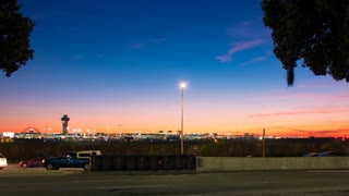 Time lapse shot of LAX airport with jet planes taking off at sunset in 4K