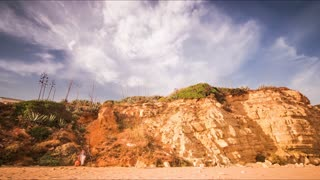 Time lapse sky above rocky cliff on sandy beach. Running clouds in blue sky over sandy rock. Rocky cliff on sandy beach sea. Moving clouds above rocky hill landscape. Coastal landscape