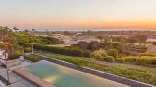 Timelapse in motion (hyperlapse) of a mordern luxury home real estate listing in Corona Del Mar, Newport Beach, California with a swimming pool, trees, orange sky at sunset with Fashion Island shopping center in view.
