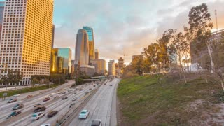 Timelapse in motion (hyperlapse) shot at sunset facing downtown Los Angeles at twilight with the sky changing from day to night with beautiful gold and blue skies above and busy street traffic next to trees below.