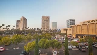 Timelapse in motion or hyperlapse at sunset turning from day into night with high rise buildings lights turning on in Fashion Island shopping district located in Newport Beach, California with palm trees and cars in the foreground