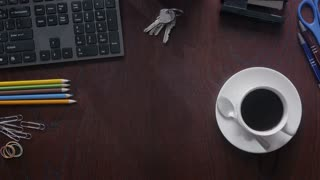 Timelapse of using phone, taking notes and typing on desktop. Flat top view of a person working at the wooden desk an drinking coffee as day passes.