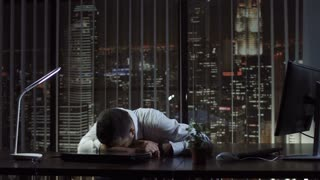 Tired businessman lying and sleeping on desk in office at night