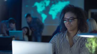 Tired young african woman hardworker in modern late at night office closing the laptop and taking off glasses and close her eyes