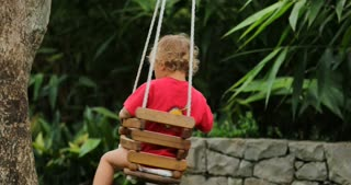 Toddler Baby Boy Playing By Himself On A Backyard Swing