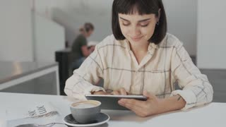 Top side view on young entrepreneur girl is working outdoor in big industrial coworking center or cafe, using her portablee tablet with touch screen to text mails or make presentations
