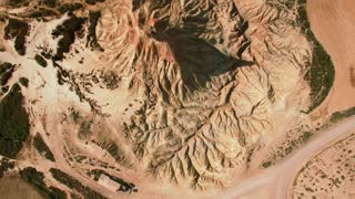 Top view drone footage flying over high peak in national reserve park dry and beige desert, erosian made geological mountain pillar, drought resulted landscape, global warming threat