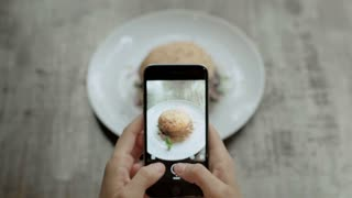 Top view of food blogger or social media influencer makes photos of her amazing huge mouth watering fast food burger on smartphone, obsessed with publishing online