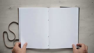 Top view on big a4 notebook with blank mockup papers, isolated on clean white wooden table. Hands turn some pages and hold still. Loop video, education and presentation business concept