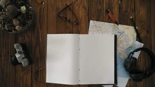 Top view on layout of travel essentials of modern man on wooden table, big notebook, planner or organizer lays open with white empty sheets, place for your text, gets picked up by hipster hands