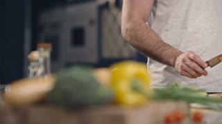 Tracking shot of man slicing bell pepper for salad on wooden cutting board on kitchen counter and putting it into glass bowl