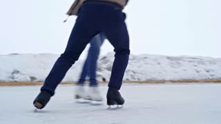 Tracking with low-section of legs of man and woman in casual clothing figure skating and practicing tricks on outdoor ice rink