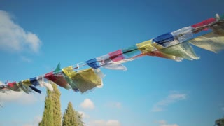 Traditional religious buddhist prayer flags with colorful cloth fabric flap in strong wind in tibet or india, on top of mountain in temple or basecamp. Symbols of peace, strength and wisdom
