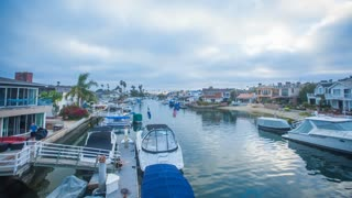Twilight time-lapse or hyperlapse in Newport Beach harbor with clouds overhead at sunset with boats, yachts and coastal homes in the background.