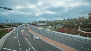 Twilight time-lapse or hyperlapse in Newport Beach over Pacific Coast Highway (PCH) with traffic below and clouds overhead. Shot at sunset with cars, coastal homes and street lights in the background.