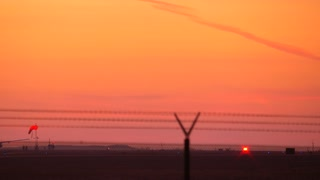 Twin engine jet plane taking off in silhouette against an orange sky sunset from LAX airport with sound