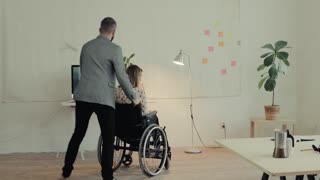 Two business people in the office. A man and woman in a wheelchair working together