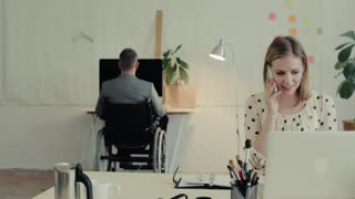Two business people in the office. A man in a wheelchair and woman with smartphone working together
