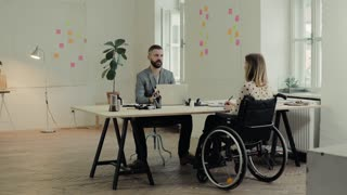 Two business people in the office working together. A man and woman in a wheelchair consulting a project