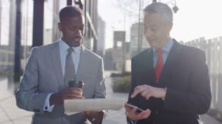 Two business professionals walk and talk over share prices in a paper, in slow motion