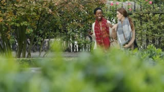 Two diverse friends walking through city gardens talking, in slow motion