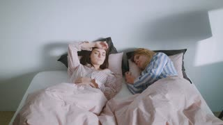 Two girl friends or a homosexual couple are lazily waking up in the morning in their big and comfy bed, happily smile and laugh