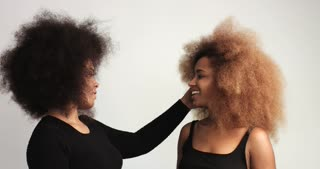 two girls swith huge afro hair recived an ice cream each one and surprized.