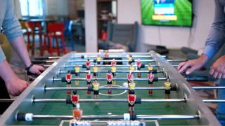 Two Guys Play Table Football in startup office