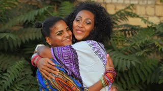 Two happy beautiful afro-american women friends hugging outdoor in park. Multi ethnic girls wearing colorful clothing enjoys the meeting and laughing in slow motion. Dolly shot