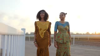 Two happy beautiful afro-american women friends walking outdoor. Multi ethnic girls wearing african long dresses communicates, enjoys the meeting and laughing in slow motion. Dolly shot