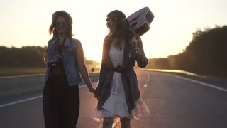 Two hippie girls walk along the freeway at dawn. slow motion
