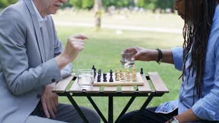 Two men dispute a chess move during a game outdoors in the park