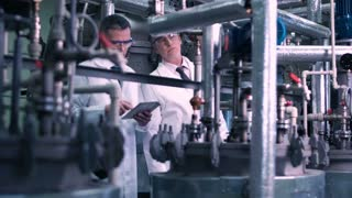 Two men with the tablet standing and making a research on a factory. Horizontal indoors shot