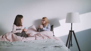 Two pretty best friends females, a blonde and a brunette are drinking coffee and have woman talk in the bed with pastel sheets in the morning, while wearing their bright pajamas