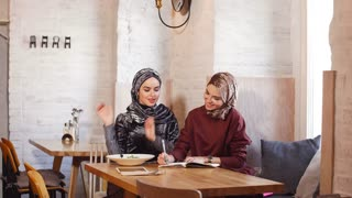 Two pretty muslim women with hijab in cafe. Sitting on couches at a table and talking.