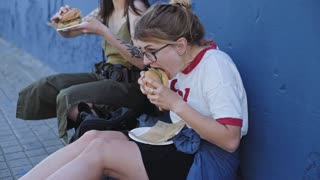 Two pretty young female girls chill near a textured blue wall munch on artisanal fast food street market hamburger both vegan and carnivore