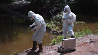Two scientists in protective suits exploring nature and taking sample of water in river
