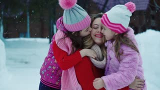Two small daughters hug and kiss on Mom for a walk. Mother and childrens are walking in the winter forest. slow motion