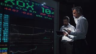 Two stock broker team leaders in front of a live, futuristic global market feed