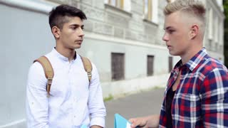 Two teenage students in front of university talking.
