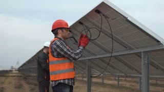 Two worker, the engineer connect cables of solar batteries