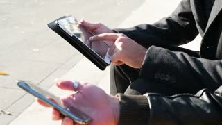 Two young businessman holding smartphone and tablet