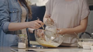 Two young ladies cooking batter for muffins: one woman pouring milk into glass bowl and another girl stirring mixture with whisk