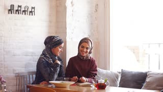 Two young muslim business woman sitting in cafe. Business lunch.