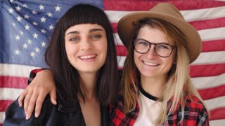 Two young students embrace and celebrate independence day in excitement and awe they laugh and giggle, hug they wear hipster clothing, hard core american jacket and flag hangs on the wall