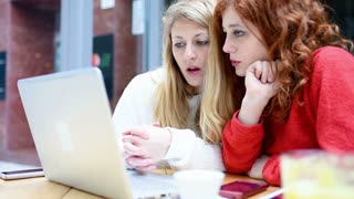 Two young women friends using computer