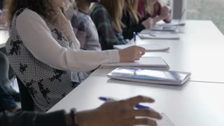 University students writing in the notebooks in a lecture. Young intelligent multi-ethnic people working on the study course in the university classroom. Higher education.