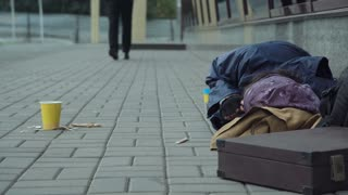 Unrecognizable passerby businessman giving hamburger to poor homeless sleeping person