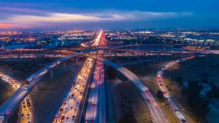 Urban aerial drone time lapse in motion or hyperlapse at night flying along an interstate with traffic showing the on and off ramp circles