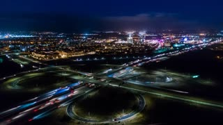 Urban aerial drone timelapse in motion or hyperlapse in the city at night flying towards a highway with cars and traffic with the on and off ramp circles and high rise buildings.
